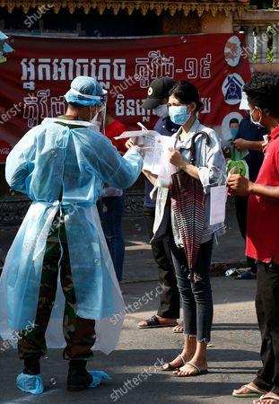 Stock Picture of A woman shows documents to a military medical worker to get a dose of COVID-19 vaccine during a vaccination drive held at a center in Phnom Penh, Cambodia, 04 May ?2021. Cambodia's Prime Minister Hun Sen ordered on 03 May 2021 an end to the lockdown of Phnom Penh and Takhmao City of Kandal Province, starting from 06 May 2021, but some high risk areas may continue to be closed.