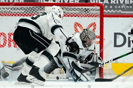 Los Angeles Kings goaltender Jonathan Quick, right, gets some help with a save from Kings right wing Dustin Brown (23) during the second period of an NHL hockey game against the Arizona Coyotes, in Glendale, Ariz