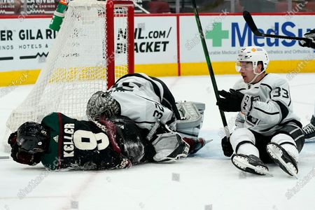 Arizona Coyotes right wing Clayton Keller (9) gets shoved into Los Angeles Kings goaltender Jonathan Quick (32) by Kings defenseman Tobias Bjornfot (33) during the first period of an NHL hockey game, in Glendale, Ariz