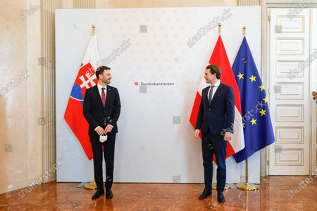 Slovakian Prime Minister Eduard Heger, is welcomed by Austrian Chancellor Sebastian Kurz prior to a press conference at the federal chancellery in Vienna, Austria