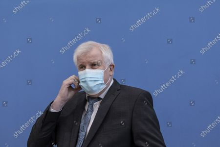German Interior Minister Horst Seehofer Pits of his protective masks prior a press conference to present the 2020 report of politically motivated crime on May 04, 2021 in Berlin, Germany. 2020 saw the highest level of politically-motivated crime in Germany since 2001, with over 44,000 registered cases that right-wing, left-wing, Reichscitizen, Islamist and other radical groups and individuals.