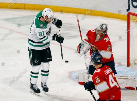 Stock Photo of Dallas Stars center Tyler Seguin (91) scores a game-tying goal past Florida Panthers goaltender Spencer Knight (30) during the third period of an NHL hockey game, in Sunrise, Fla