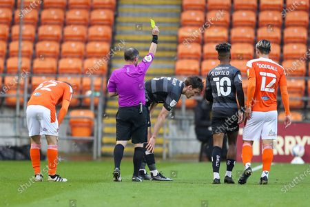 Stock Image of The Referee Robert Lewis shows a yellow card to Doncaster Rovers Defender Joe Wright (5) during the EFL Sky Bet League 1 match between Blackpool and Doncaster Rovers at Bloomfield Road, Blackpool