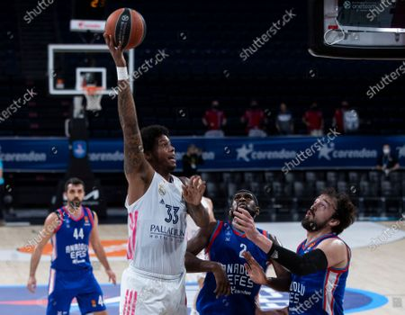 Stock Picture of Real Madrid's Trey Thompkins (L) in action against Anadolu Efes' Chris Singleton (C) and Sertac Sanli (R) during the Euroleague basketball playoff match between Anadolu Efes and Real Madrid in Istanbul, Turkey 04 May 2021.