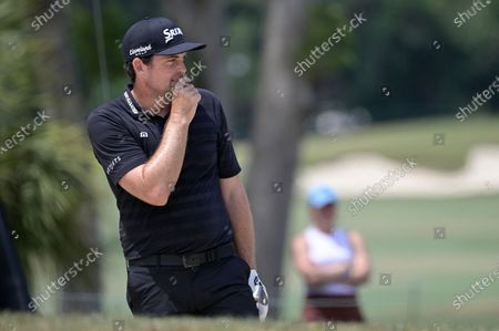Keegan Bradley reacts after hitting out of a bunker onto the 16th green during the final round of the Valspar Championship golf tournament, in Palm Harbor, Fla