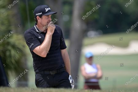 Keegan Bradley reacts after hitting out of a bunker onto the third green during the final round of the Valspar Championship golf tournament, in Palm Harbor, Fla