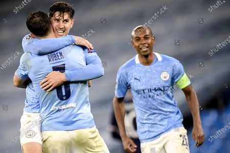 Stock Photo of Manchester City's John Stones (C), Ruben Dias (L) and Fernandinho (R) celebrate after winning the UEFA Champions League semi final, second leg soccer match between Manchester City and Paris Saint-Germain in Manchester, Britain, 04 May 2021.