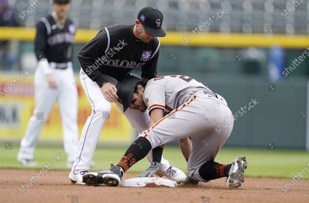 Colorado Rockies second baseman Ryan McMahon, left, applies a late tag as San Francisco Giants' Mike Tauchman slides safely into swecond bae with a double in the first inning of game one of a baseball doubleheader, in Denver