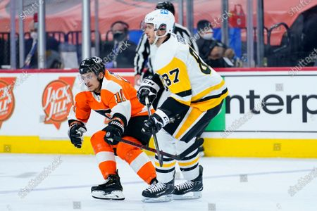 Philadelphia Flyers' Travis Konecny, left, guards Pittsburgh Penguins' Sidney Crosby during the first period of an NHL hockey game, in Philadelphia