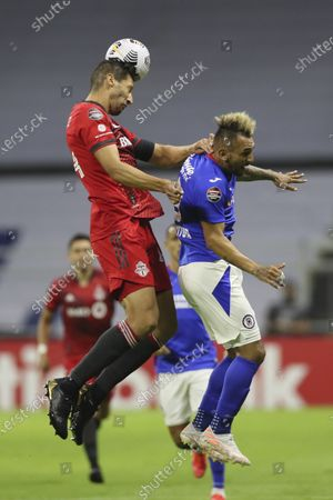 Omar Gonzalez of Canada's Toronto FC, left, clears the ball challenged by Walter Montoya of Mexico's Cruz Azul during a CONCACAF Champions League quarterfinal second leg soccer match at Azteca stadium in Mexico City