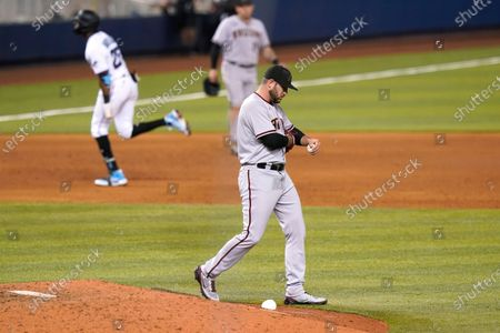 Arizona Diamondbacks relief pitcher Alex Young stands on the mound as Miami Marlins right fielder Lewis Brinson rounds the bases with a three-run home run during the eighth inning of a baseball game, in Miami. The Marlins won 9-3