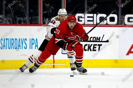 Stock Photo of Carolina Hurricanes' Warren Foegele (13) controls the puck in front of Chicago Blackhawks' Ian Mitchell (51) during the third period of an NHL hockey game in Raleigh, N.C