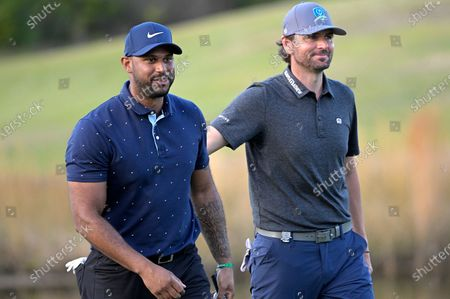 Stock Picture of Professional baseball player Aaron Hicks and former professional tennis player Mardy Fish share a laugh while walking on the 18th fairway during the final round of the Tournament of Champions LPGA golf tournament, in Lake Buena Vista, Fla