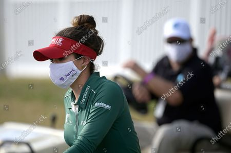 Gaby Lopez, of Mexico, wears a face mask while riding on a cart to the 18th hole during the final round of the Tournament of Champions LPGA golf tournament, in Lake Buena Vista, Fla