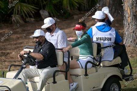 Gaby Lopez, second from right, of Mexico, and professional baseball player Josh Donaldson, second from left, wear face masks while riding on a cart to the 18th hole during the final round of the Tournament of Champions LPGA golf tournament, in Lake Buena Vista, Fla