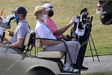 Actor Jack Wagner, center, wears a face mask while riding on a cart to the 18th hole during the final round of the Tournament of Champions LPGA golf tournament, in Lake Buena Vista, Fla
