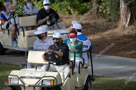 Gaby Lopez, right, of Mexico, and professional baseball player Josh Donaldson, left, wear face masks while riding on a cart to the 18th hole during the final round of the Tournament of Champions LPGA golf tournament, in Lake Buena Vista, Fla