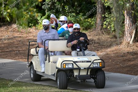 Gaby Lopez, center, of Mexico, and professional baseball player Josh Donaldson, left, wear face masks while riding on a cart to the 18th hole during the final round of the Tournament of Champions LPGA golf tournament, in Lake Buena Vista, Fla