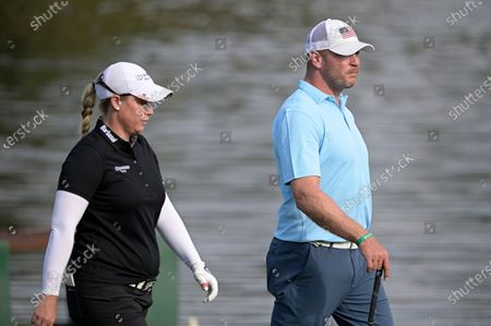 Brittany Lincicome, left, and former NFL football player Brian Urlacher walk on the 17th fairway during the final round of the Tournament of Champions LPGA golf tournament, in Lake Buena Vista, Fla