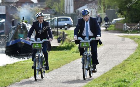 Stock Photo of British Prime Minister Boris Johnson, right, and mayor for West Midlands Andy Street ride their bikes ride along the towpath of the Stourbridge canal in the West Midlands during a Conservative party local election visit . Local elections take place in England Thursday