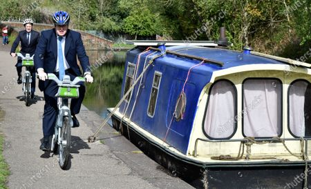 Stock Image of British Prime Minister Boris Johnson, right, and mayor for West Midlands Andy Street ride a bike ride along the towpath of the Stourbridge canal in the West Midlands during a Conservative party local election visit . Local elections take place in England Thursday