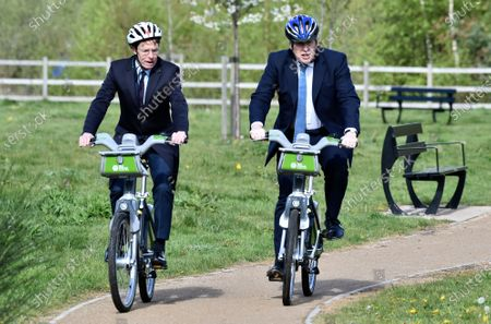 British Prime Minister Boris Johnson, right, and mayor for West Midlands Andy Street ride their bikes near the towpath of the Stourbridge canal in the West Midlands during a Conservative party local election visit . Local elections take place in England Thursday