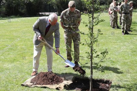 Stock Picture of Prince Charles helps plant a tree next to Commanding Officer, Lieutenant Colonel Henry Llewelyn-Usher as he visits members of the Welsh Guards at Combermere Barracks