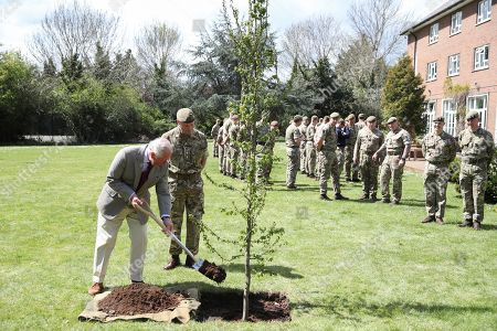 Stock Photo of Britain's Prince Charles helps plant a tree next to Commanding Officer, Lieutenant Colonel Henry Llewelyn-Usher as he visits members of the Welsh Guards at Combermere Barracks, in Windsor, Britain