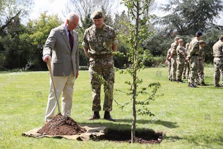 Stock Image of Britain's Prince Charles helps plant a tree next to Commanding Officer, Lieutenant Colonel Henry Llewelyn-Usher as he visits members of the Welsh Guards at Combermere Barracks, in Windsor, Britain