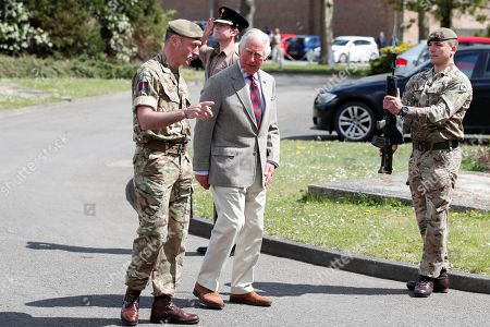 Prince Charles walks with Commanding Officer, Lieutenant Colonel Henry Llewelyn-Usher past Quarter guard as he arrives to visit members of the Welsh Guards at Combermere Barracks