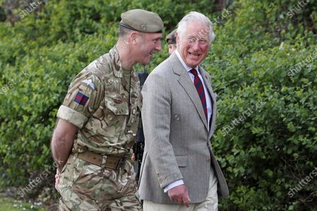Britain's Prince Charles walks with Commanding Officer Lieutenant Colonel Henry Llewelyn-Usher as he arrives for a visit to Combermere Barracks in Windsor, England