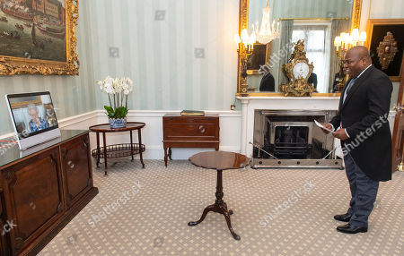 Queen Elizabeth II appears on a screen via videolink from Windsor Castle, where she is in residence, during a virtual audience to receive the Ambassador of Haiti Euvrard Saint Amand at Buckingham Palace, London.