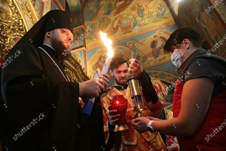Governor of the St Michael's Golden-Domed Monastery Ahapit lights candles with the Holy Fire delivered to Ukraine from Jerusalem during the welcome ceremony at  St Michael's Golden-Domed Cathedral, Kyiv, capital of Ukraine.