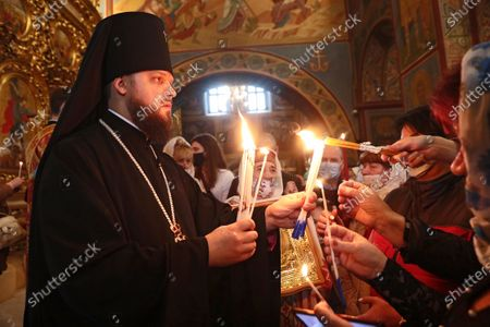 Devotees light their candles with the Holy Fire delivered to Ukraine from Jerusalem during the welcome ceremony at St Michael's Golden-Domed Cathedral, Kyiv, capital of Ukraine.