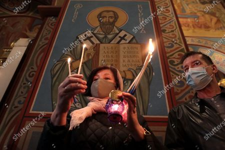 A woman holds candles during the welcome ceremony of the Holy Fire delivered to Ukraine from Jerusalem at St Michael's Golden-Domed Cathedral, Kyiv, capital of Ukraine.