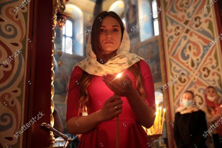 A woman shields a candle with the hand during the welcome ceremony of the Holy Fire delivered to Ukraine from Jerusalem at St Michael's Golden-Domed Cathedral, Kyiv, capital of Ukraine.