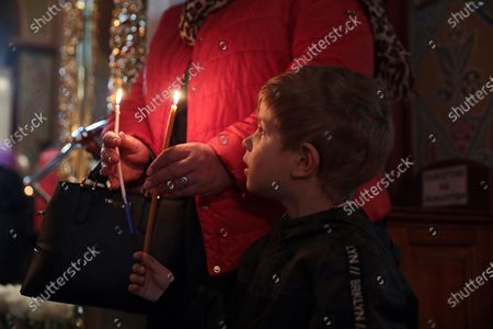 A boy looks at a candle during the welcome ceremony of the Holy Fire delivered to Ukraine from Jerusalem at St Michael's Golden-Domed Cathedral, Kyiv, capital of Ukraine