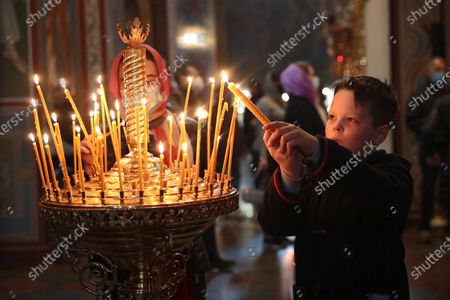 A boy lights a candle during the welcome ceremony of the Holy Fire delivered to Ukraine from Jerusalem at St Michael's Golden-Domed Cathedral, Kyiv, capital of Ukraine.
