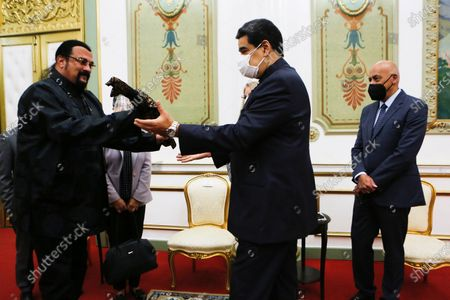 In this handout photo provided by the Miraflores Press Office, actor Steven Seagal, left, presents Venezuela's President Nicolas Maduro with a Samurai sword, at the presidential palace in Caracas, Venezuela