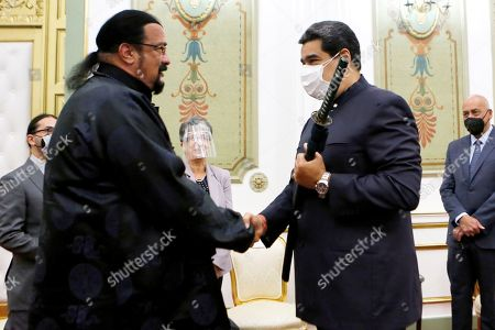 In this handout photo provided by the Miraflores Press Office, actor Steven Seagal, left, and Venezuela's President Nicolas Maduro shake hands after Seagal presented Maduro with a Samurai sword, at the presidential palace in Caracas, Venezuela