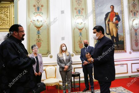 Stock Image of In this handout photo provided by the Miraflores Press Office, Venezuela's President Nicolas Maduro holds the Samurai sword that was given to him by actor Steven Seagal, left, accompanied by first lady Cilia Flores, center, and National Assembly President Jorge Rodriguez, at the presidential palace in Caracas, Venezuela