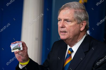 Agriculture Secretary Tom Vilsack holds up a Supplemental Nutrition Assistance Program Electronic Benefits Transfer (SNAP EBT) card during a press briefing at the White House, in Washington