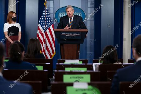 White House press secretary Jen Psaki listens as Agriculture Secretary Tom Vilsack speaks during a press briefing at the White House, in Washington