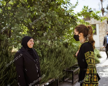 Queen Rania, wearing a face mask, meets with a group of small income-generating project owners