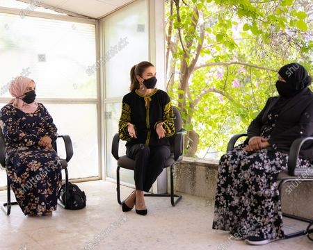 Stock Picture of Queen Rania, wearing a face mask, meets with a group of small income-generating project owners