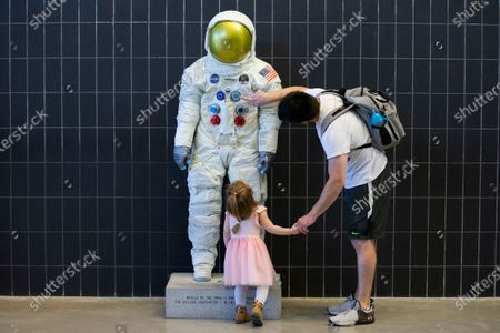 Stock Picture of Benjamin Stancik and his daughter look at a statue depicting the spacesuit worn by late US astronaut Neil Armstrong, at the National Air and Space Museum's Steven F. Udvar-Hazy Center in Chantilly, Virginia, USA, 05 May 2021. The National Air and Space Museum's Steven F. Udvar-Hazy Center is the first Smithsonian museum to reopen to the public since closing for the COVID-19 coronavirus pandemic. Six more Smithsonian museums and the National Zoo will reopen to the public later in May, 2021.
