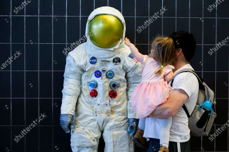 Benjamin Stancik and his daughter look at a statue depicting the spacesuit worn by late US astronaut Neil Armstrong, at the National Air and Space Museum's Steven F. Udvar-Hazy Center in Chantilly, Virginia, USA, 05 May 2021. The National Air and Space Museum's Steven F. Udvar-Hazy Center is the first Smithsonian museum to reopen to the public since closing for the COVID-19 coronavirus pandemic. Six more Smithsonian museums and the National Zoo will reopen to the public later in May, 2021.