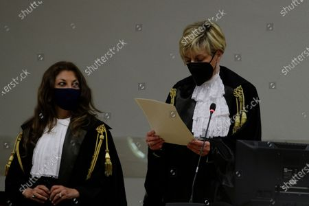 Judge Marina Finiti, right, reads the verdict in the trial for the slaying of an Italian plainclothes police officer, in Rome, . A jury in Rome has convicted two American friends in the 2019 slaying of a police officer in a drug sting gone awry, sentencing them to life in prison. The jury delivered more than 12 hours before delivering the verdicts late Tuesday against 21-year-pld Finnegan Lee Elder and 20-year-old Gabriel Natale