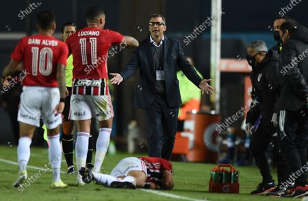 Racing's coach Juan Antonio Pizzi (C) argues with Sao Paulo players while forward Martin Benitez (below) complains of a blow, during the Group E match of the Copa Libertadores between Racing Club and Sao Paulo, at the Presidente Peron 'El Cilindro' stadium, in Avellaneda, Argentina, 05 May 2021.