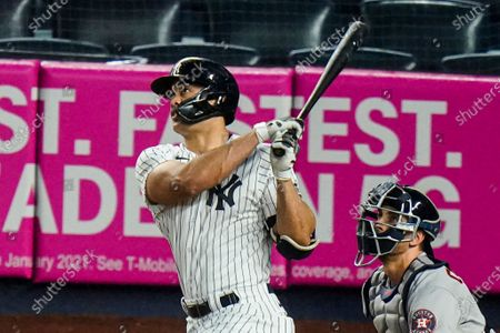 New York Yankees' Giancarlo Stanton follows through on a two-run home run during the third inning of a baseball game against the Houston Astros, in New York